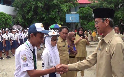 Wakil Wali Kota Djainuddin Damopolii usai menyematkan tanda peserta Ujian Nasional kepada salah satu siswa