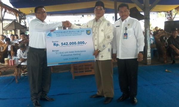 Direktur Bank Sulut Cabang Lolak Keneddy Paputungan saat menyerahkan bantuan kepada Bupati Bolmong Salihi Mokodongan.