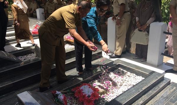 Pj Bupati Adrianus Nixon Watung didampingi istri saat tabur bunga disalah satu makan mantan bupati
