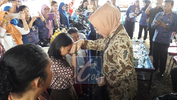 Wali Kota Kotamobagu Tatong Bara saat memberikan bantuan sekolah kepada salah satu siswa di acara pelayanan terpadu di kampung KB