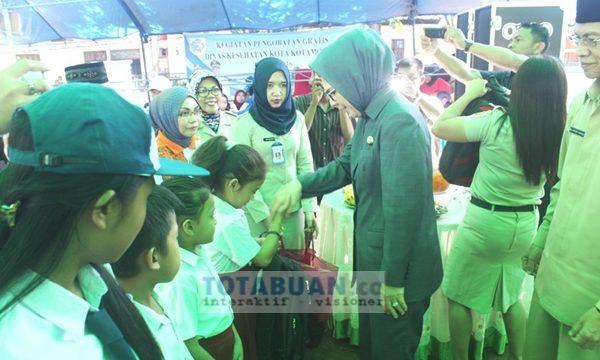 Wali Kota Tatong Bara dan Wakil Wali Kota Jainudin Damopolii saat memberikan bantuan kepada siswa kurang mampu