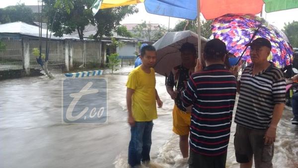 Kondisi air yang melupa hingga ke jalan dan masuk ke pemukiman warga. Tampak kondisi air di Kelurahan Sinindian