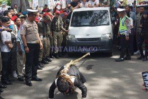 Aksi Limbad saat menarik mobil berpenumpang di HUT Kotamobagu
