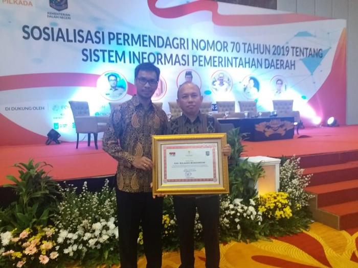 Kepala Bappeda Bolmong Yarlis Awaludin Hatam saat menerima  penghargaan dari Menteri Dalam Negeri (Mendagri) Tjahjo Kumulo karena telah berhasil mengintegrasikan pengerjaan dan penganggaran berbasis elektronik ke dalam Sistem Informasi Pemerintah Daerah (SIPD)