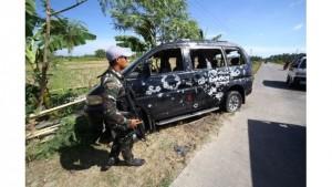 Seorang tentara berjaga di samping mobil yang rusak akibat baku tembak dengan pemberontak Muslim